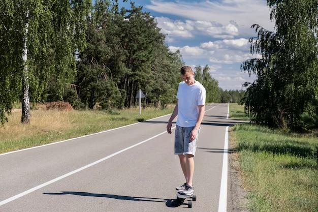 森と青い空を背景にアスファルトの上スケートボード若い成人男性