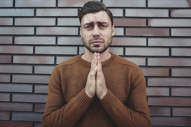 白いレンガの壁の上に立っている若い成人男性は、非常に感情的で心配している顔に希望の表現と一緒に物乞いと手で祈っています