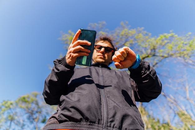 봄이나 여름에 해질녘 공원에서 스포츠를 하기 위해 휴대 전화와 smartwatch를 동기화하는 젊은 성인 남자. 개념 스포츠 개인 관리 및 기술