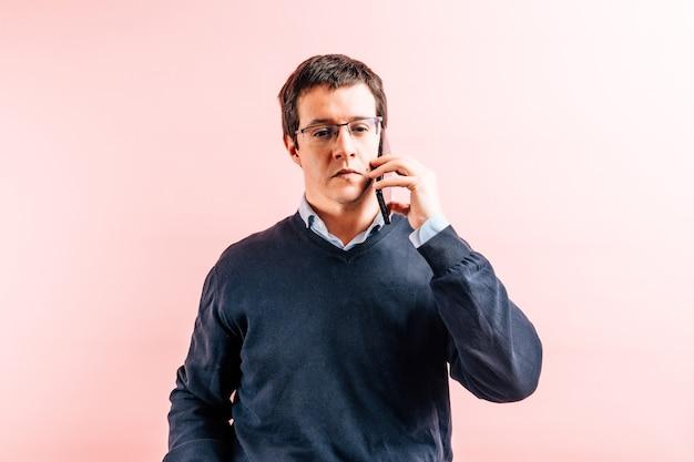 青いvネックシャツとピンクの背景のセーターを着た35歳の若い成人男性がスマートフォンで真剣に話している
