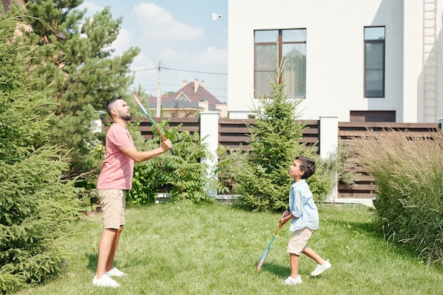 裏庭の芝生の上で彼の幼い息子とバドミントンをしているカジュアルな服を着ている若い成人男性、側面図のショット
