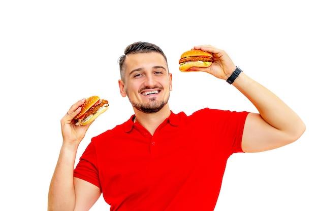 흰색 배경에 맛있는 신선한 큰 햄버거를 먹는 수염을 가진 젊은 성인 남자