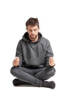 白で隔離された、あぐらをかいて座って瞑想する若い大人。彼は灰色のスウェットシャツとズボンを着ています。