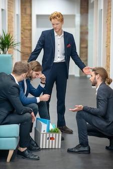 사무실 복도에서 손으로 몸짓을 논의하는 비즈니스 정장에 젊은 성인 남성
