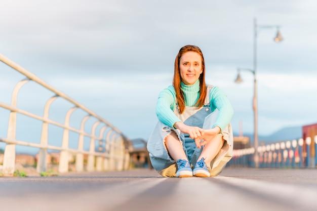 Молодая взрослая женщина-миллениал, сидящая на дорожных линиях на закате, улыбаясь, одетая в повседневную одежду