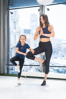 Young adult mother and little daughter together practicing yoga