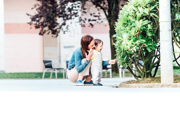 公園で彼女の1歳の息子に植物を教える若い大人の母親