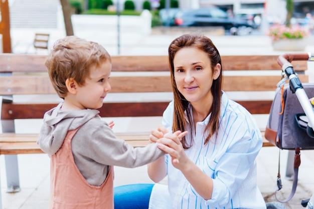ワイプで路上で息子の手を拭く若い大人の母親