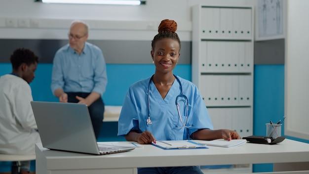 ノートパソコンで机に座っている若い大人の看護師