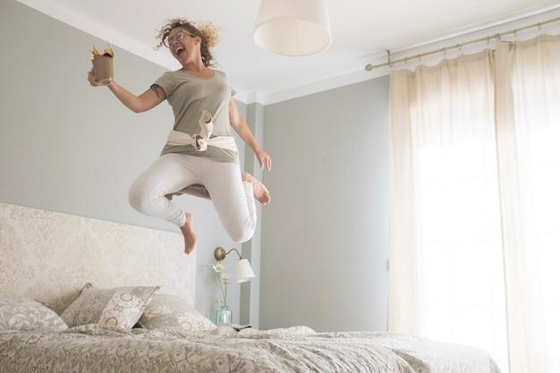 若い大人のきれいな女性が幸せに夢中になり、コーヒー カップを持ってベッドに飛び乗る