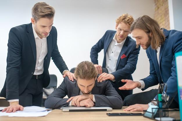 Молодые взрослые серьезные коллеги-мужчины во время работы в офисе жестикулируют и обсуждают результат