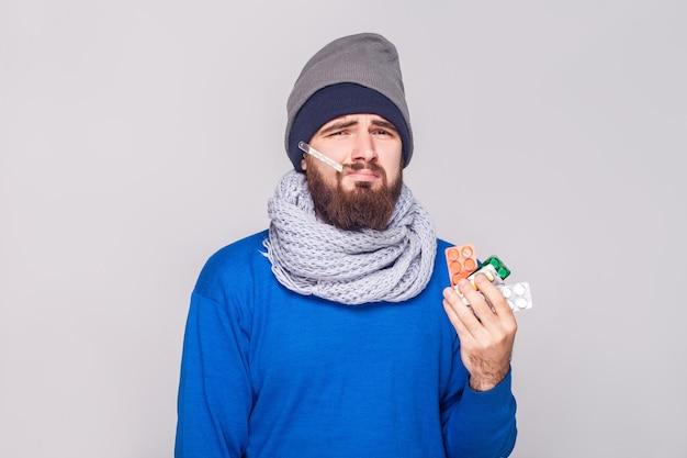 若い成人の病人は、多くの錠剤を保持している温度を持っています