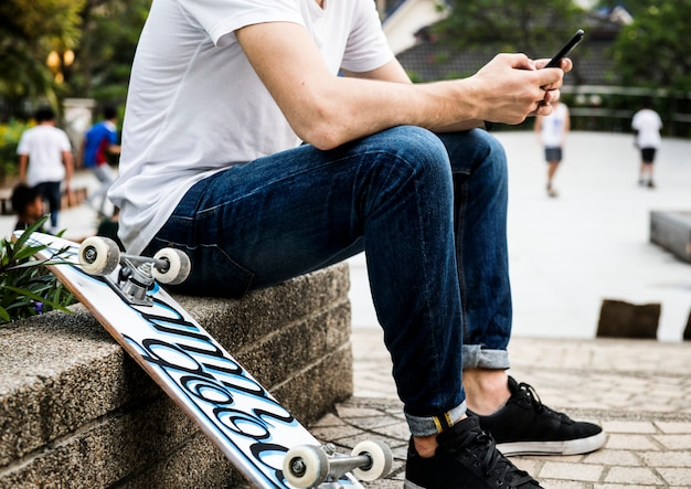 Young adult skateboarder using a smartphone