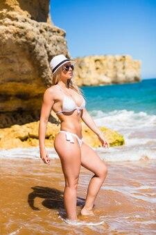 海のビーチのポーズの若い大人のスリムな魅力的な女性