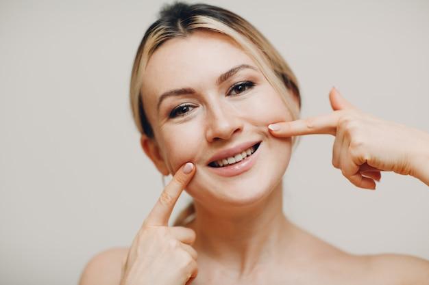 Молодая взрослая женщина с улыбкой делает лицевую гимнастику, самомассаж и омолаживающие упражнения, наращивание лица для лифтинга кожи и мышц