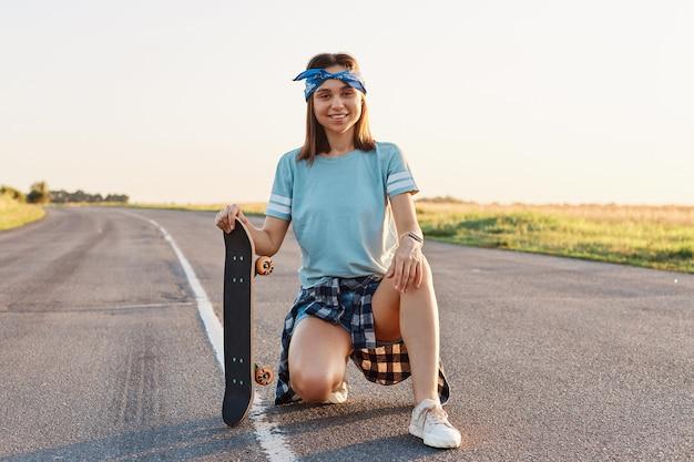 Giovane femmina sorridente adulta con aspetto piacevole accovacciata all'aperto su strada asfaltata e tenendo lo skateboard, riposando dopo aver guidato, guardando la telecamera con espressione felice.