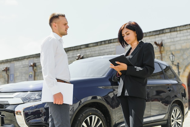 タブレットを使用して車の近くに立っているビジネスダークスーツの若い大人の笑みを浮かべて男と女