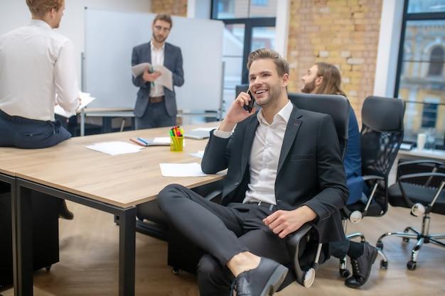 Молодой взрослый улыбающийся человек со смартфоном в кресле и коллегами в чате после презентации
