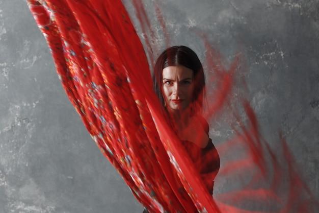 Молодая взрослая испанская женщина танцует фламенко на сером винтажном студийном фоне с размытием движения