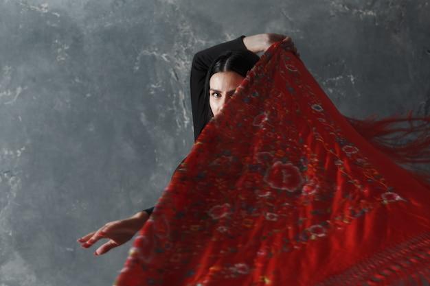 Молодая взрослая испанская женщина танцует фламенко на сером фоне старинных студии
