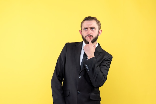 Young adult thinking about high resolution with his suit on yellow