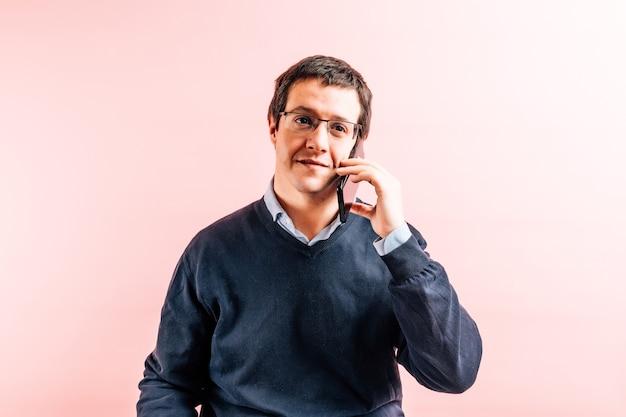 Молодой взрослый тридцатипятилетний мужчина в синей рубашке с v-образным вырезом и свитере с розовым фоном улыбается, разговаривает по смартфону