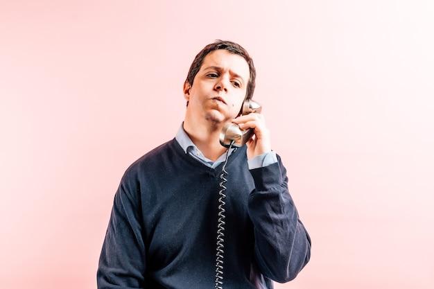 Молодой взрослый тридцатипятилетний мужчина в синей рубашке с v-образным вырезом и свитере на розовом фоне разговаривает по проводному телефону, попыхивая от получения плохих новостей