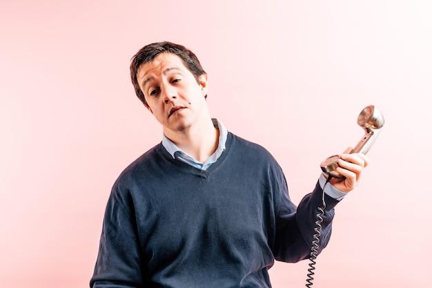 Молодой взрослый тридцатипятилетний мужчина в рубашке и синем свитере с v-образным вырезом на розовом фоне скучно отворачивается от своего лица жестом отчаяния