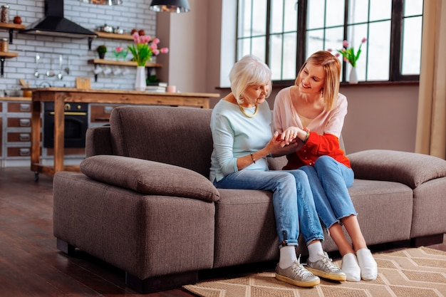 Young adult volunteer discussing with an aging woman on sofa