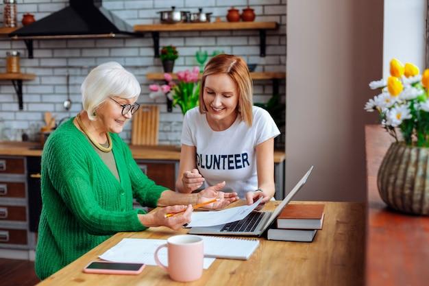 キッチンで年配の女性と話し合う若い大人のボランティア