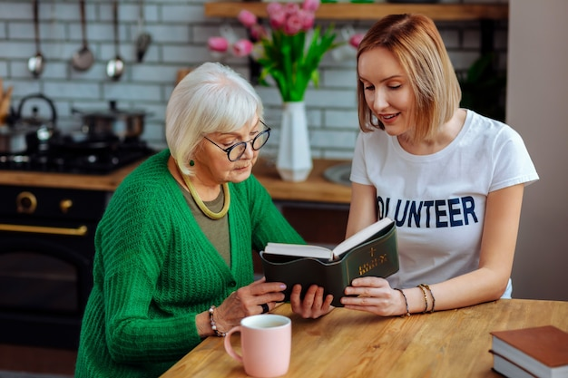 부엌에서 노인 여성과 논의하는 젊은 성인 자원 봉사자