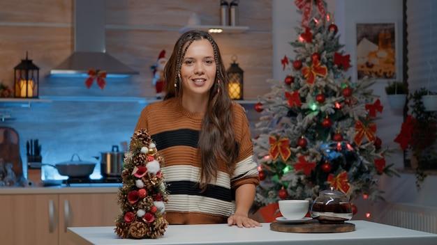 Giovane adulto che saluta la telecamera per videochiamate in cucina festiva