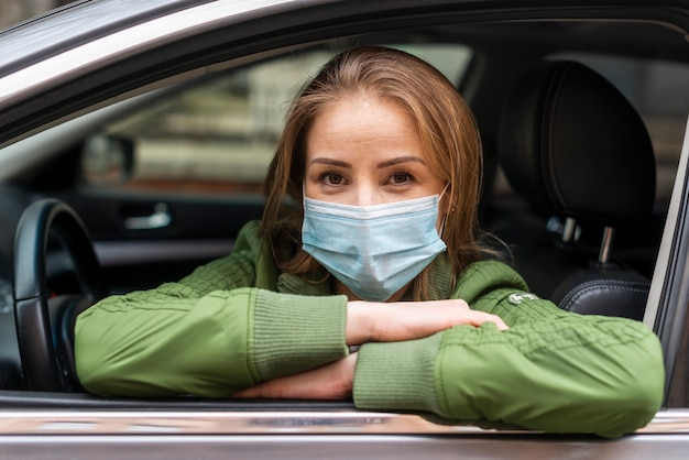 Young adult wearing a protection mask in the car