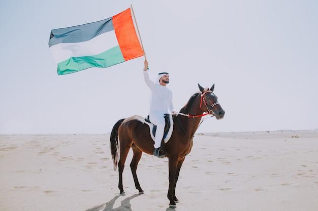 Молодой взрослый с кандурой, традиционной одеждой эмиратов, едет верхом на лошади в пустыне