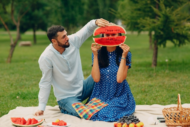 スイカを楽しんで公園の緑の草の牧草地で若い大人の女性と男性のカップルのピクニック