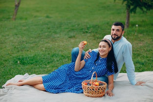 公園の緑の草の牧草地に座っている若い大人の女性と男性のカップルのピクニック。