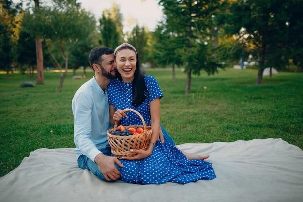 公園の緑の草の牧草地でフルーツバスケットと座っている若い成人女性と男性のカップルのピクニック。