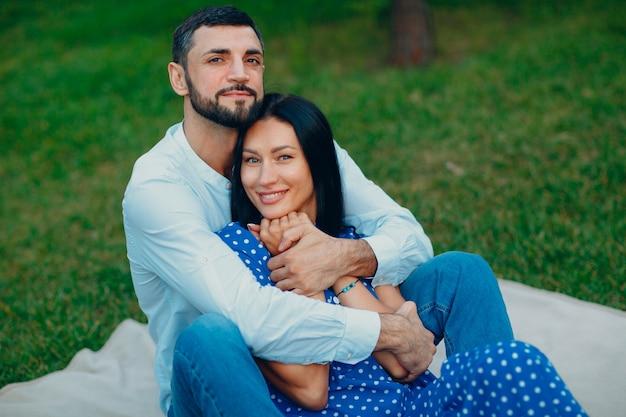 若い成人女性と公園の緑の草の牧草地でカップルのピクニックを抱き締める男。