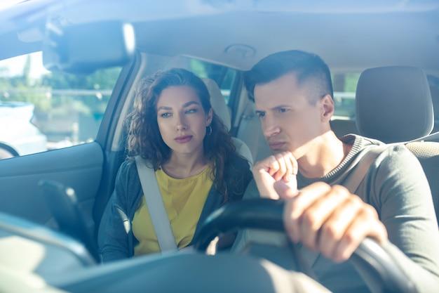 若い大人の女性と新しい車のインテリアの男