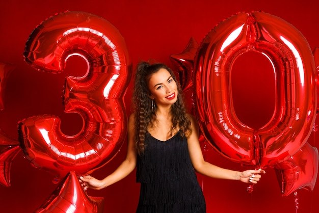 A young adult woman on a background of red balloons in the shape of the number thirty  model brunett...