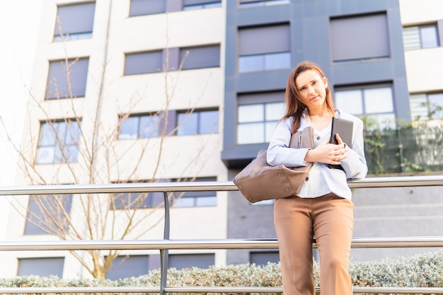 Young adult woman beautiful businesswoman holding the business tablet. successful business woman concept. copy space. real estate business concept