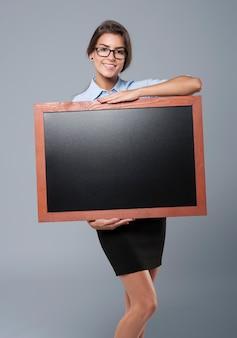空の黒板を運ぶ若い大人の女性