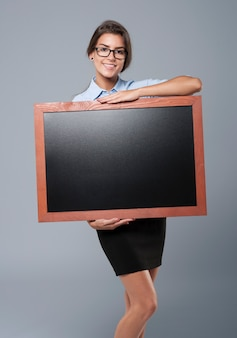 Young adult woman carrying an empty blackboard