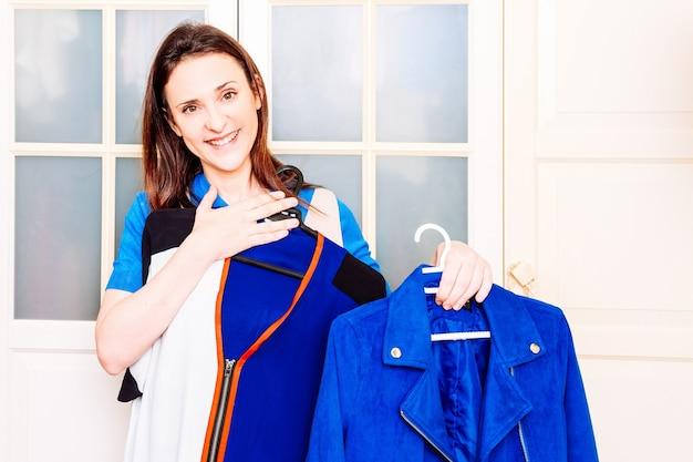 春や夏の服をチェックして注文する若い大人の女性。コンセプトは季節に応じてワードローブを並べ替えます