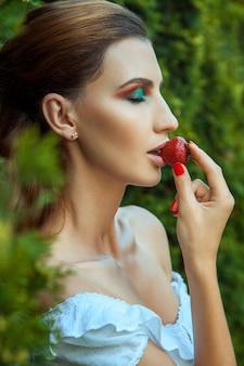 若い大人の女性は目を閉じて、赤い甘いイチゴを食べています。屋外の春または夏の写真