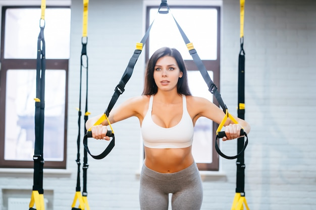 Young adult woman doing exercises in the gym