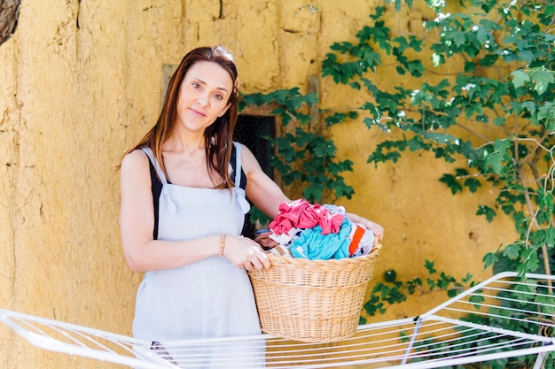 Young adult woman doing laundry in the garden