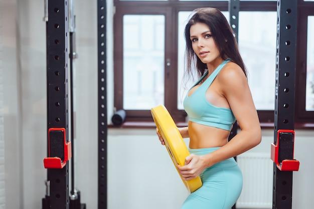 Молодая взрослая женщина делает силовые упражнения в тренажерном зале