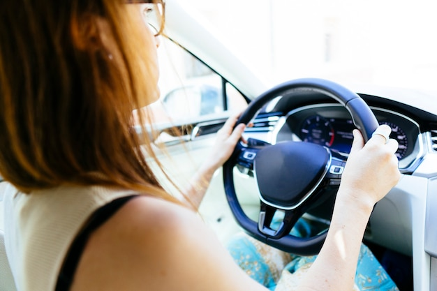 Young adult woman driving a modern car