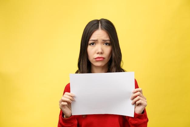 恥と驚きの顔にショックを受けた白紙のシートを保持している若い大人の女性